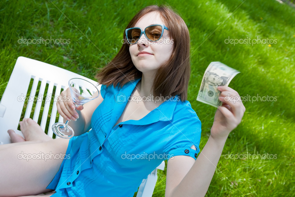 Woman sitting on the lounge and holding a wineglass with a bankn
