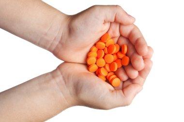 Orange tablets in children's palms