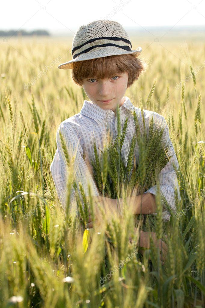 Boy is among the ears of wheat