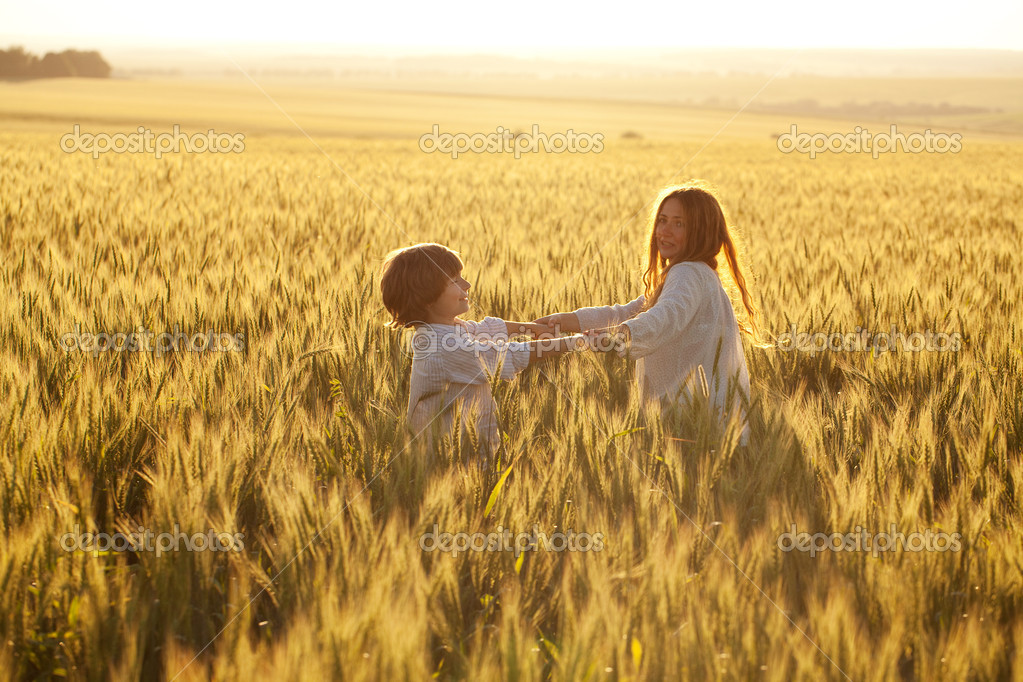 Happy mother and son are running through a wheat field