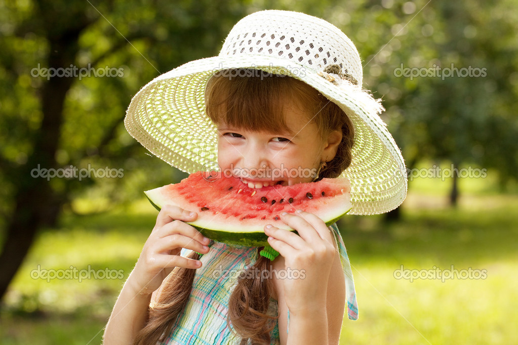 Girl in the hat and dress eating a watermelon