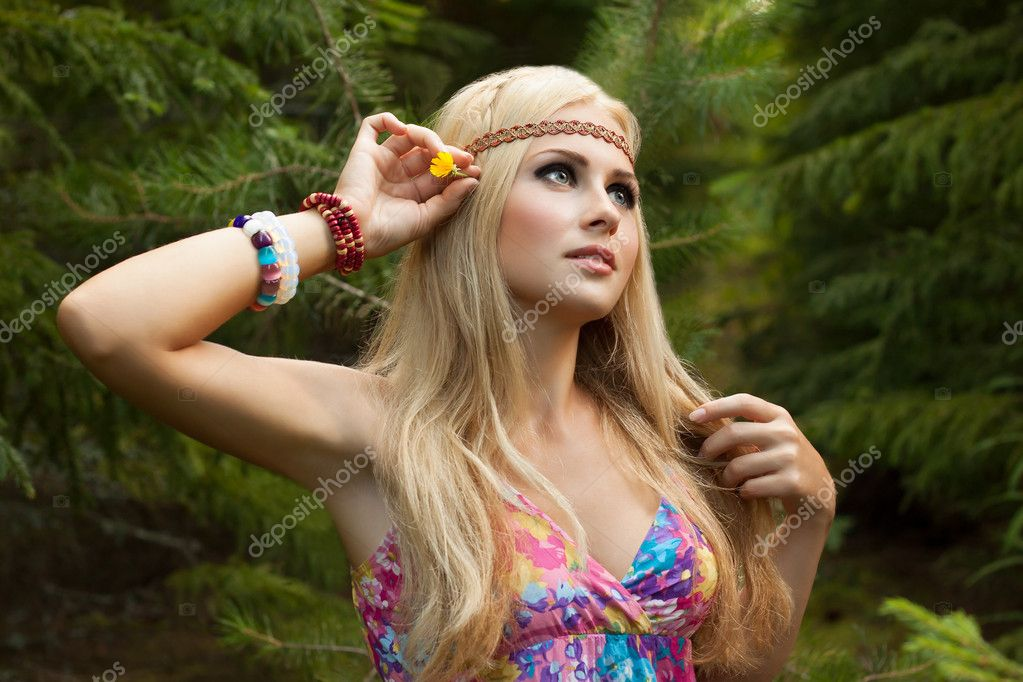 Beautiful young woman in wood decorates hair with flower
