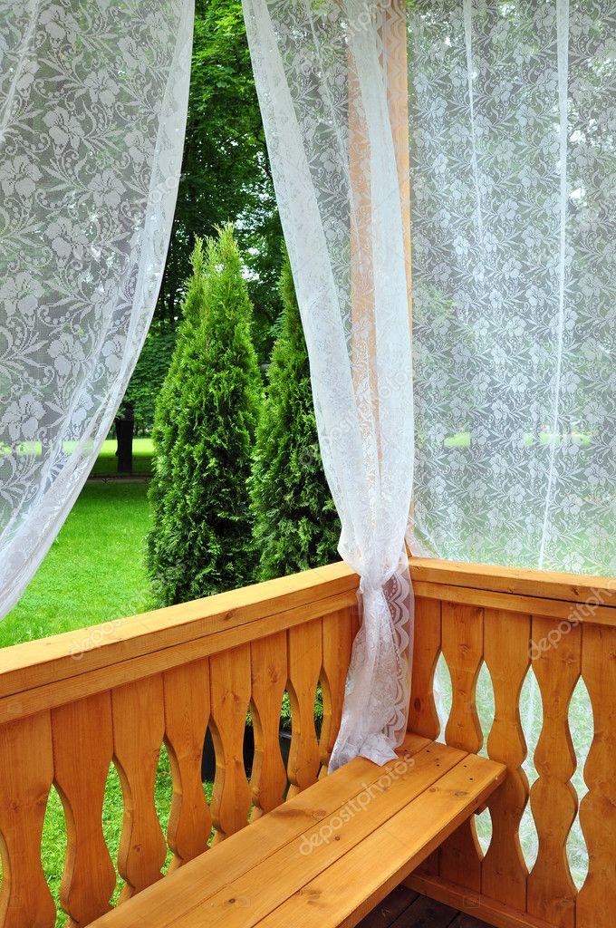 houten veranda met kant gordijnen en uitzicht op de tuin — Stockfoto ...