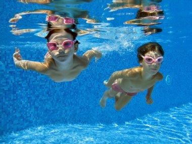 Happy smiling underwater children in swimming pool