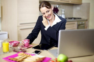 Businesswoman at home during breakfast on the phone