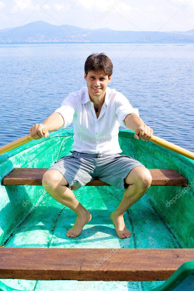 Handsome man on green wood boat rowing
