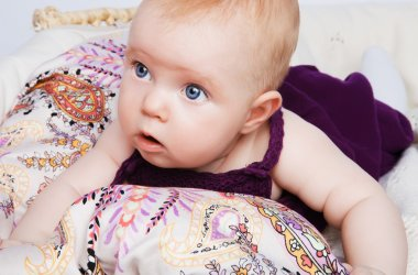 Fashion baby girl lying on a beautiful fabric in the basket and