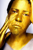 The boys head painted with gold paint stares into the camera.