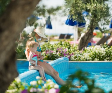 Mother with baby sitting on pool side