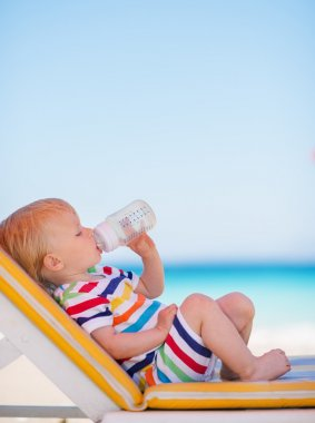 Portrait of baby on sun bed drinking water