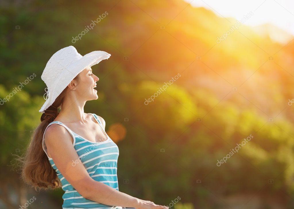 Portrait of happy woman on vacation enjoying sunset
