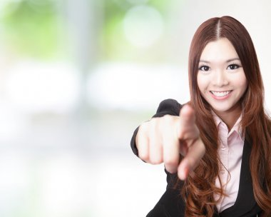 Excited business woman pointing at you and smiling