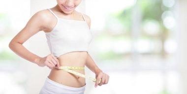 Woman smile measuring shape of waist