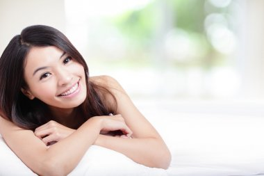 Charming woman Smile face and lying on bed
