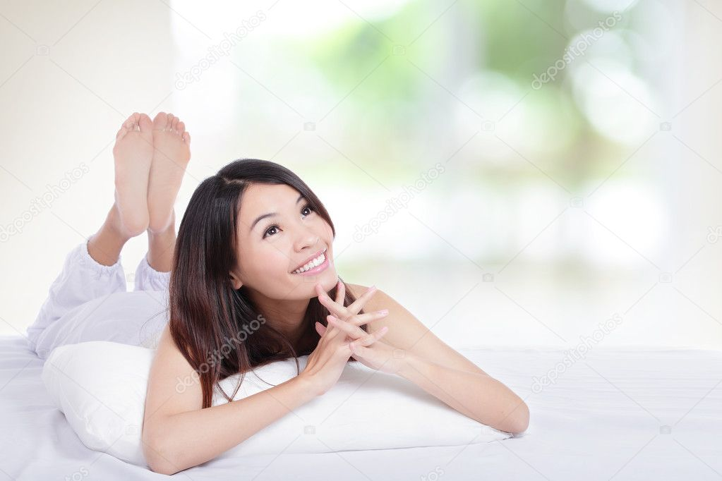 Charming woman lying on bed and looking copy space