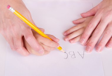 Mother or teacher helping child to write