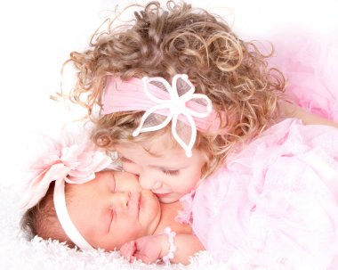 Toddler kissing her baby sister