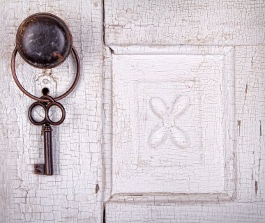 Vintage key hanging on a vintage door