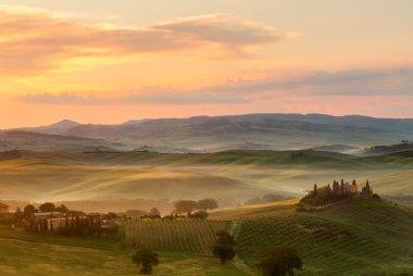 Tuscan villa in the fog on a misty sunrise morning