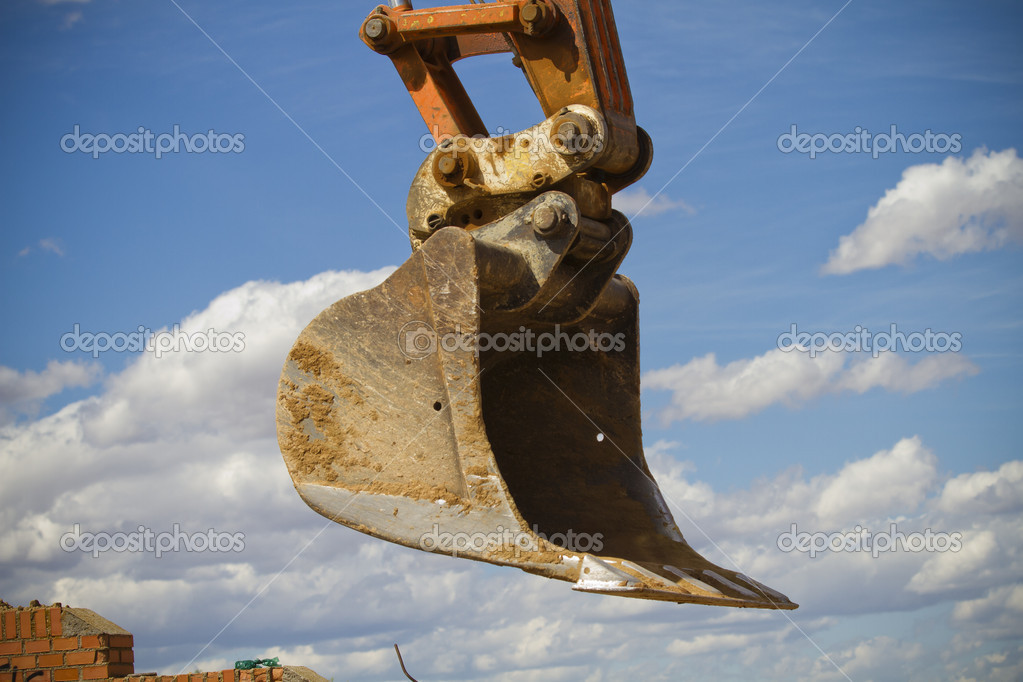 Excavator against cloud sky