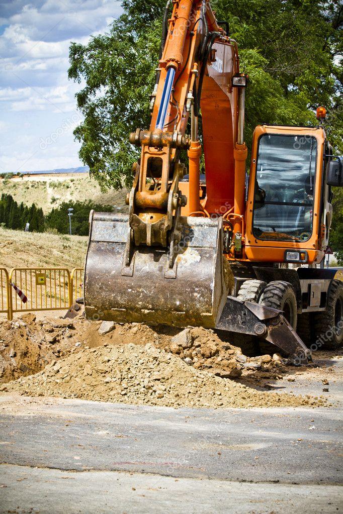 Wheel loader Excavator with backhoe unloading sand at eathmoving