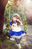 Photo Alice girl in a fairy country is riding on a swing in a garden