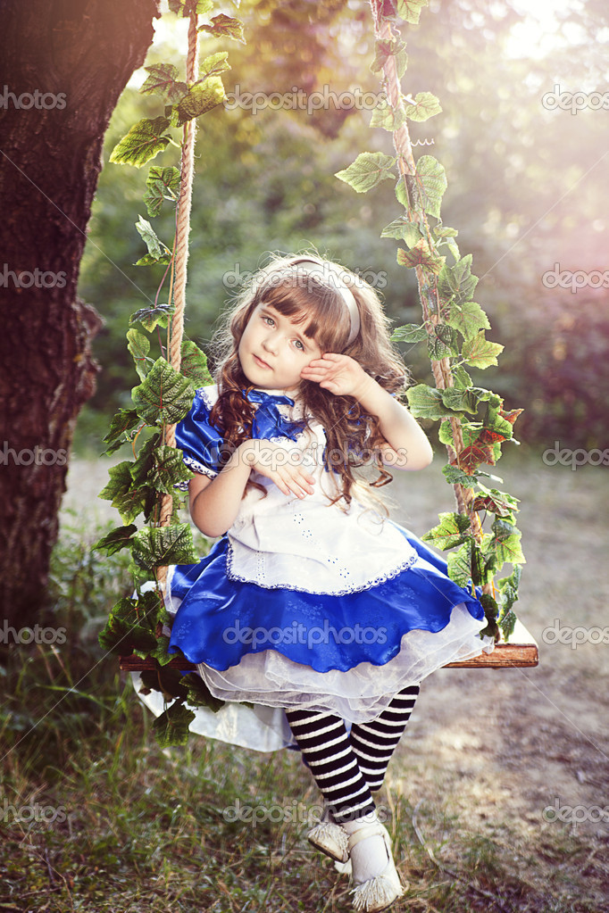 Alice girl in a fairy country is riding on a swing in a garden