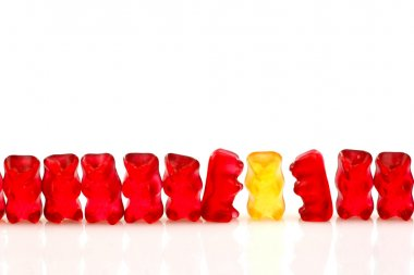 Row of red gummy bears and a single yellow one
