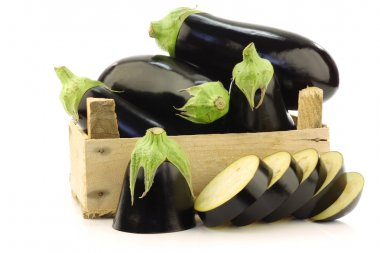 Fresh aubergines and a cut one in a wooden crate