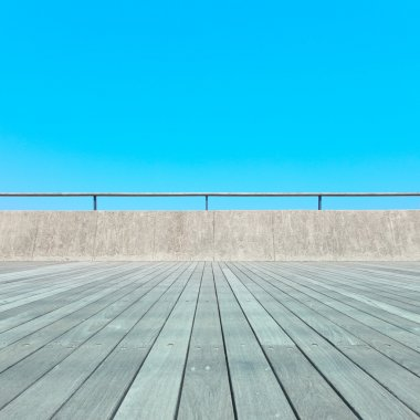 Balcony, Wood plank floor, concrete fence, blue sky. Bottom view