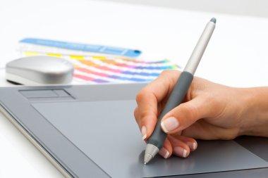 Female hand using pen on digital tablet.