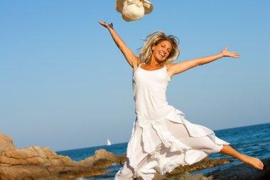 Happy woman jumping on beach.