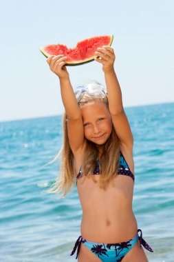 Cute girl holding piece of watermelon.