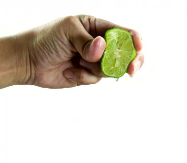 Hand squeezing juice from a green lime.
