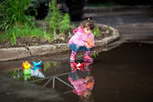 Photo Girl playing in puddles