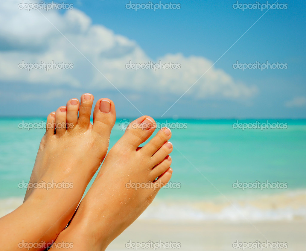 Vacation Concept. Woman's Bare Feet over Sea background