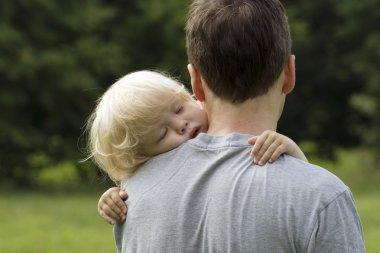 Little boy sleeping on dad's shoulder