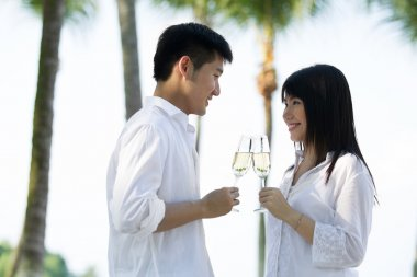 Asian couple drinking champagne.