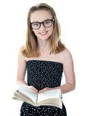 Photo Cute little girl standing with an open book