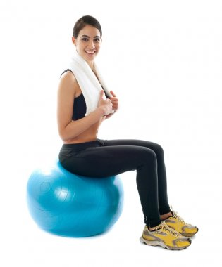 Female fitness trainer sitting on ball