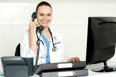 Young smiling physician sitting in clinic