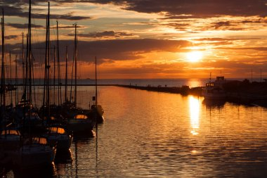 Sailboats silhouette in harbor with sunset