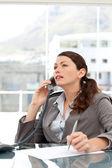 Vážné podnikatelka na telefonu a psaní poznámek
