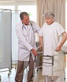 Vedoucí lékař pomoci pacientovi chodit