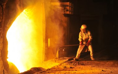 Worker takes a sample at steel company