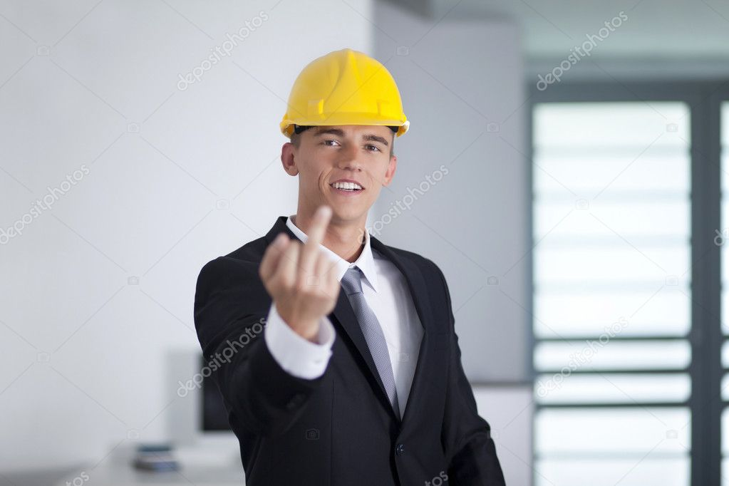 Young businessman wearing a safety hat and finger gesturing fuck