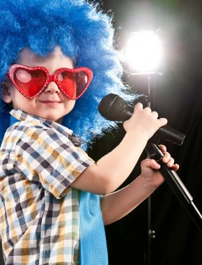 Boy sings into a microphone