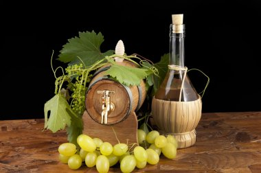 In oak casks with vines and grapes white and black