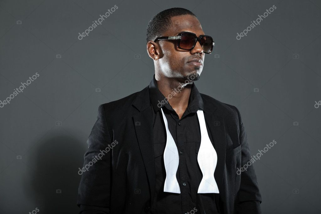 1f740185218c Cool black american man in dark suit. Studio fashion shot isolated on grey  background. Wearing dark sunglasses.– stock image