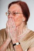 Portrét dobře vypadající starší ženy nosit brýle s expresivní tváří ukazovat emoce. strach a strach. jednají mladí. Studio záběr izolované na šedém pozadí